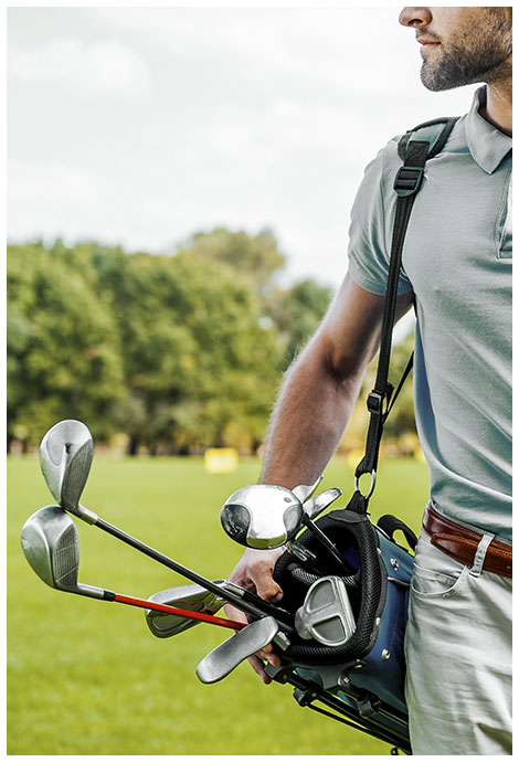 man with golf clubs slung over his shoulder